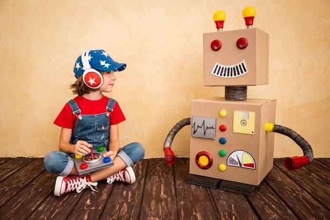 Junge sitzt neben selbstgebastelten Roboterfreund