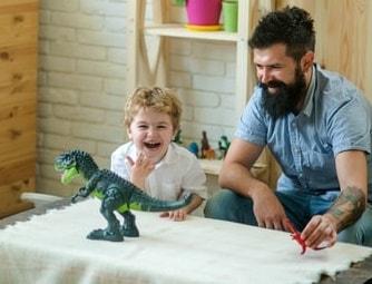 Vater spielt mit Sohn und Dino Roboter