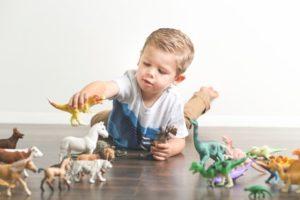 Kleinkind mit Spielzeug Dinosaurier
