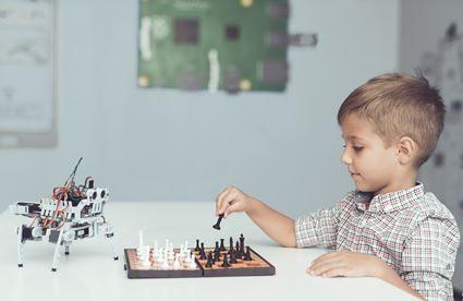 Lernroboter spielt Schach mit Jungen